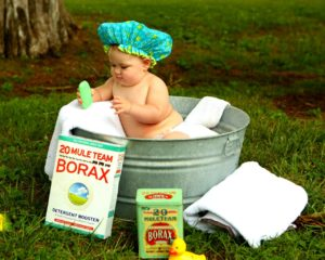 baby in galvanized steel bathtub outdoors