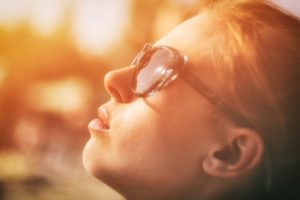 woman in sunglasses basking in sunlight